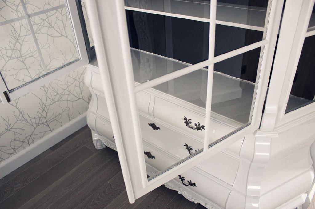Wystylizowane drzwi antycznej witryny wzbogacone srebrnym sznurkiem.